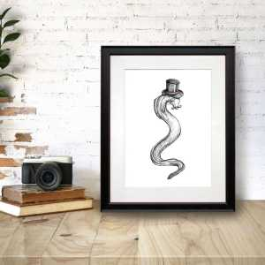 "Black and white print of an eel wearing a top hat with the text ""Genteel"" in a black frame on a wooden desk"