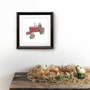 Print of a pig driving a red tractor in a dark wood frame on a white wall above a wooden shelf covered in vegetables