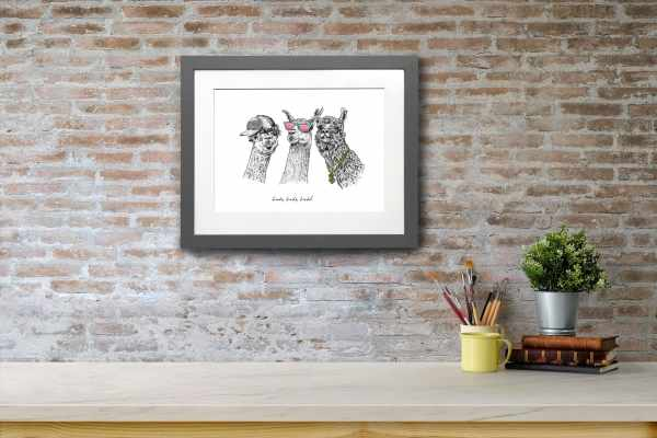Print of three black and white llamas wearing sunglasses, a cap and a gold chain in a grey frame on a red brick wall