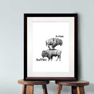 Black and white print of a buffalo standing on top of another buffalo in a dark wood frame sitting on two wooden stalls