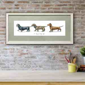 Print of three dachshunds holding each other's tails in a line in a white frame with a green mount on a red brick wall