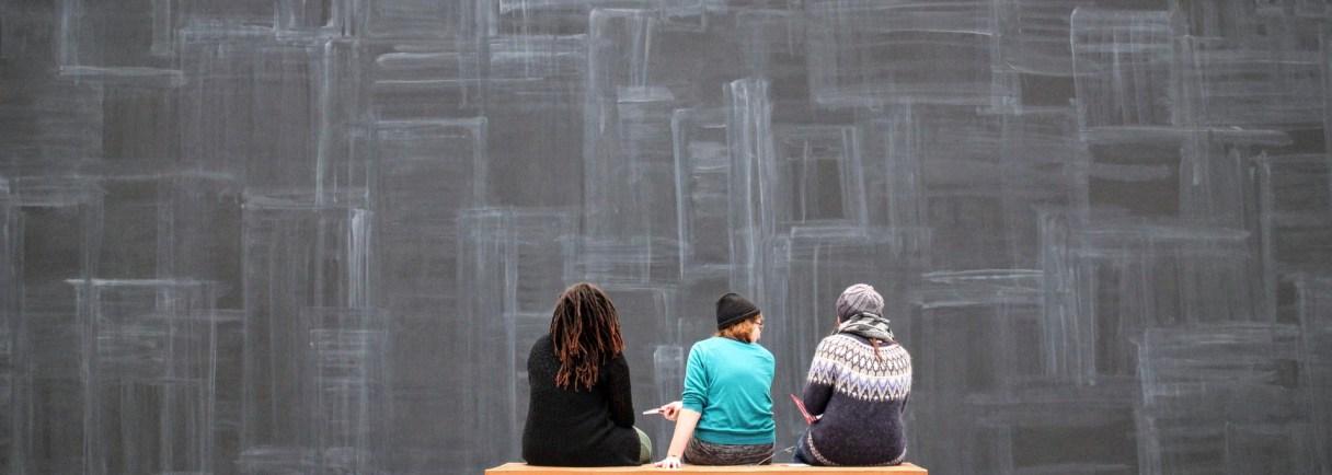 3 Personen sitzen vor einer Wand in einer Ausstellung