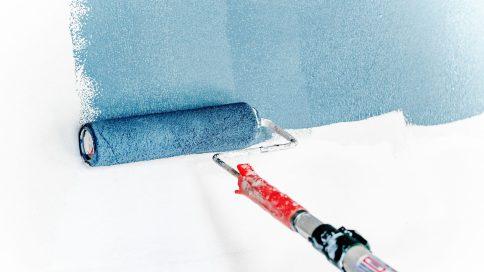 Blaue Wandfarbe wird mit Farbroller aufgetragen