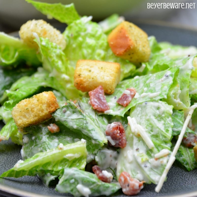 Easy bacon caesar salad is a simple combination of the basic Caesarsalad ingredients of romaine lettuce, parmesan cheese, caesardressing and croutons and taken up a notch with the addition of bacon.