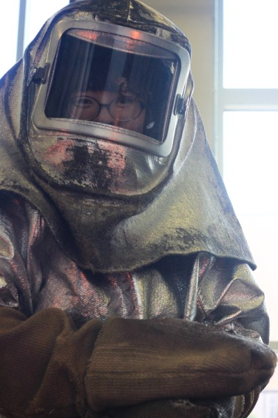 Meng Du in protective clothing in the glass studio at Rochester Institute of Technology