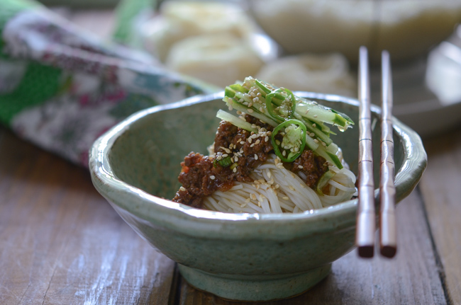Korean Noodles are topped with Beef Sauce and cucumber slices.