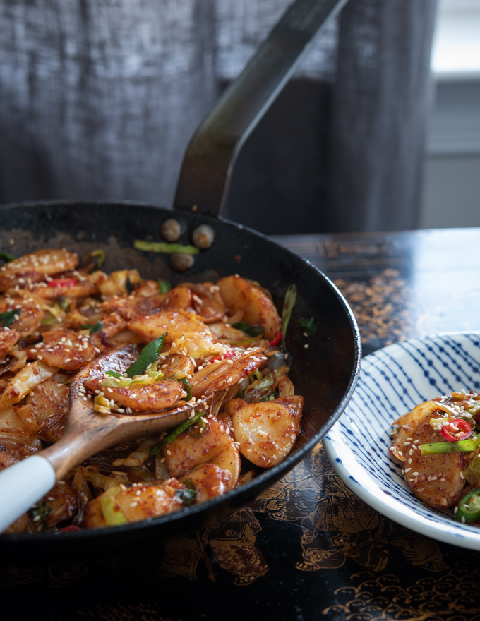 Rice cakes are stir-fried with vegetables in a skillet