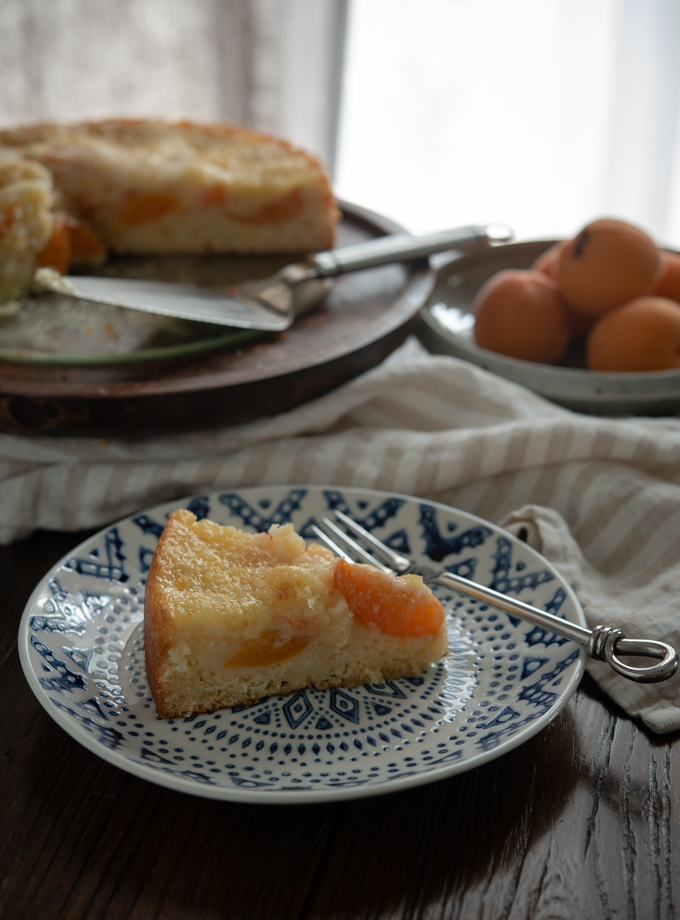 A slice of apricot Kuchen (German apricot cake) is served on a plate