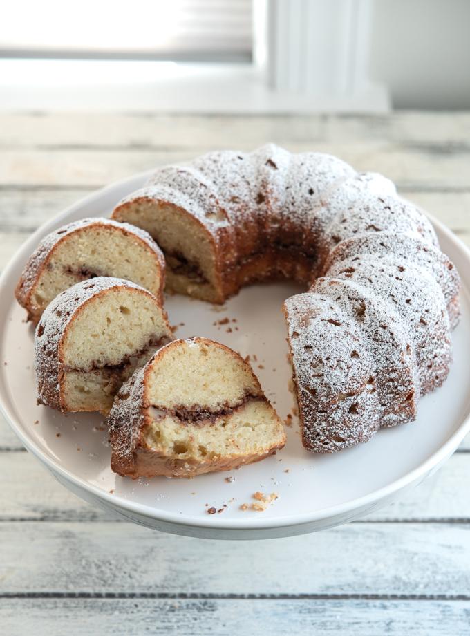 Apple Cinnamon Bundt Cake is sliced on a cake stand