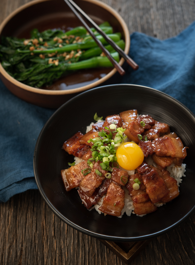 Teriyaki pork belly is served with rice and an egg yolk in a bowl