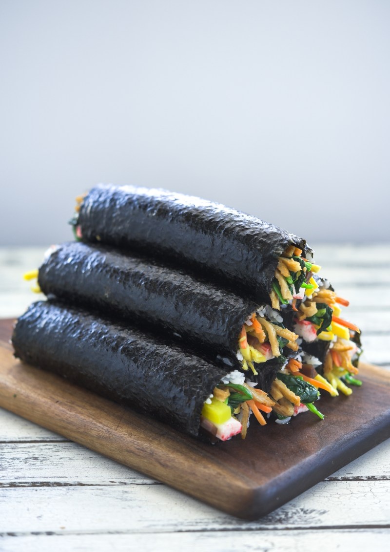 Rolled Korean seaweed rice rolls are stacked together on a cutting board