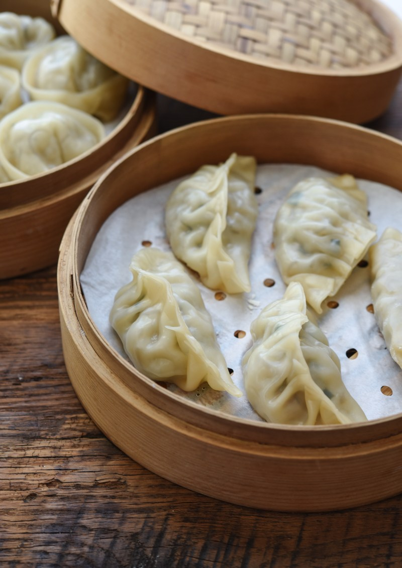 A Pleated shaped Korean dumplings are steamed in a bamboo steamer