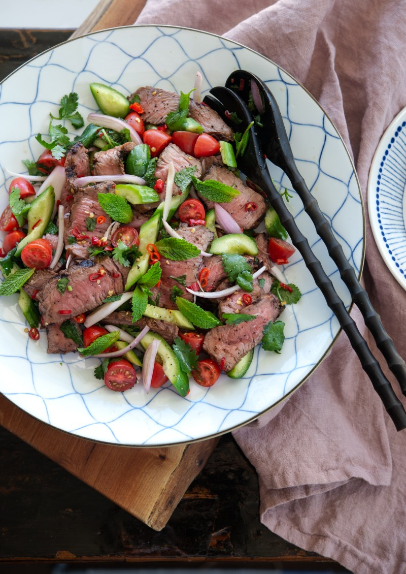 Thai beef salad is tossed with cucumber, tomato,  shallot, and fresh red chili.