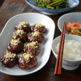 Tteok-galbi, Korean short rib patties, are glazed and topped with pine nuts