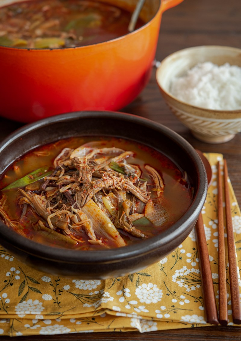 Yukgaejang (spicy Korean beef soup) is served with rice.
