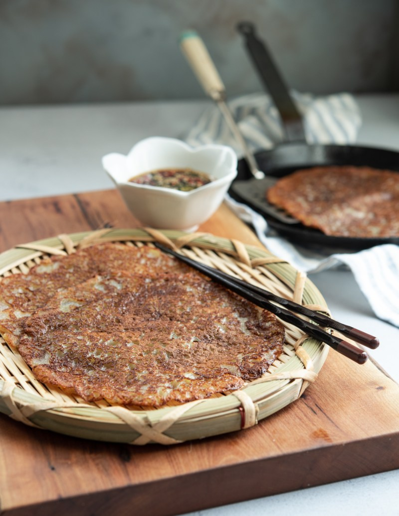 Golden crisp potato pancakes are served on a woven wooden plate with a pair of chopstick and soy chili dipping sauce