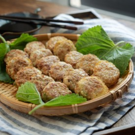 Korean meat tofu patties are served on a bamboo bastket with perilla leaves