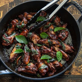 Taiwanese three cup chicken wings (san bei ji) are adorned with glaze and fresh Thai basil leaves