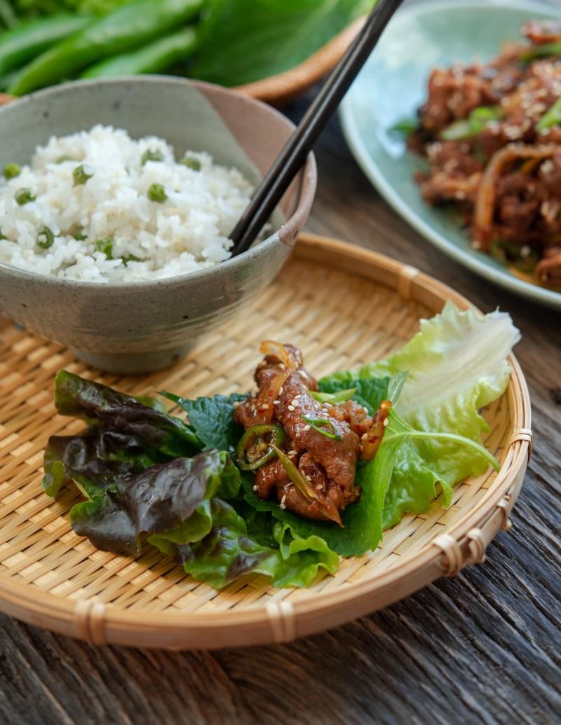 Korean pork bulgogi as a lettuce wrap is served with rice.