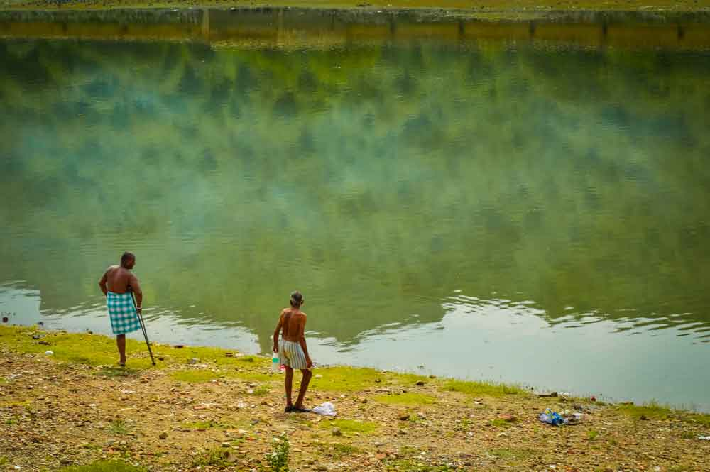 Two men at a lake by Lake by Jaigarh Fort