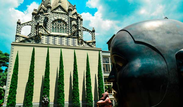 Statue at Botero Square Medellin Colombia with blue skies in the back