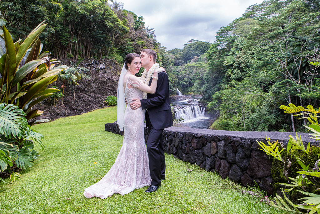 Hawaii wedding elopement bride and groom embrace by waterfall the falls at reeds island professional photographer
