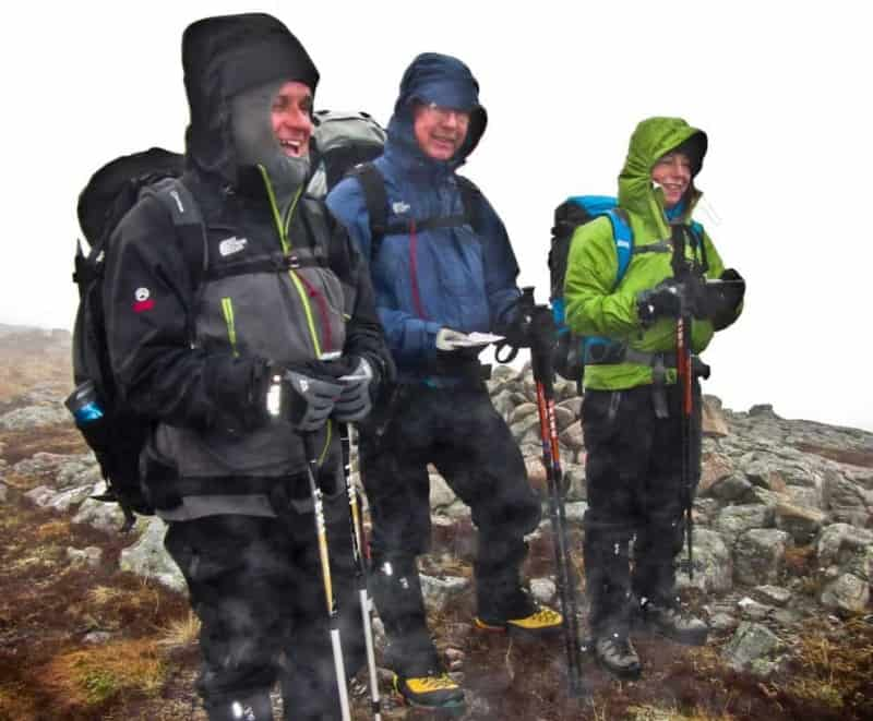 3 people stand on a summit in Snowdonia whilst on their Mountain Leader award assessment.