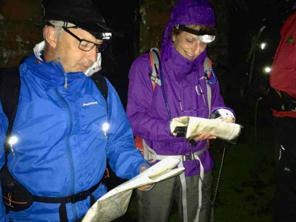 A man and a lady study their maps by torchlight on a night navigation course in the Peak District.