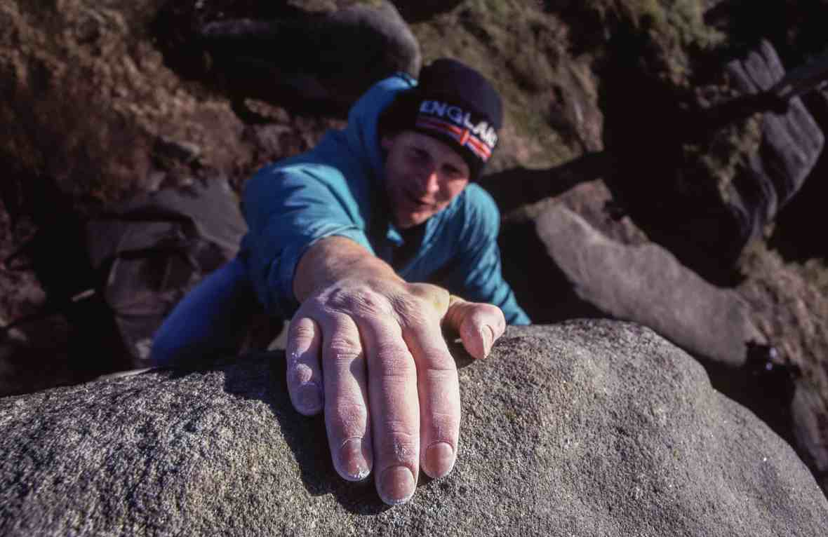 A man bouldering on gritstone in the Peak District.