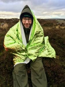 A man practices with an emergency blanket on a Mountain Leader training course.