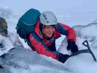 A lady learning winter skills in Scotland with ice axe and crampons