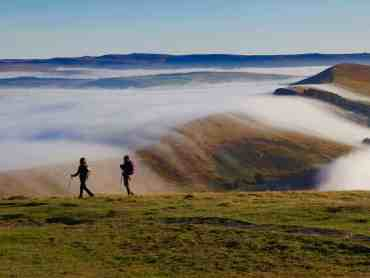 Two ladies stand on Mam Tor in the Peak District whilst on a guided walking holiday.