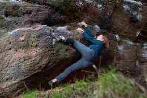 woman bouldering on a rock wearing blue bouldering pants and green top