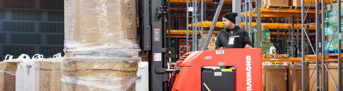 Equipment operator moving inventory with forklift