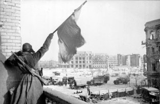 A Soviet soldier waving a flag in victory at the Battle of Stalingrad, the largest, deadliest battle in history. Source: Georgii Zelma [1] - This image was provided to Wikimedia Commons by the German Federal Archive
