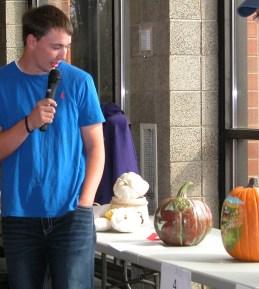 Male livestock judging student evaluating pumpkins