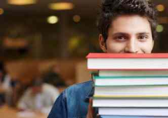 male student with stack of books