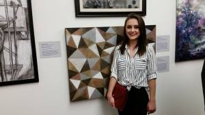 Student standing next to art on display
