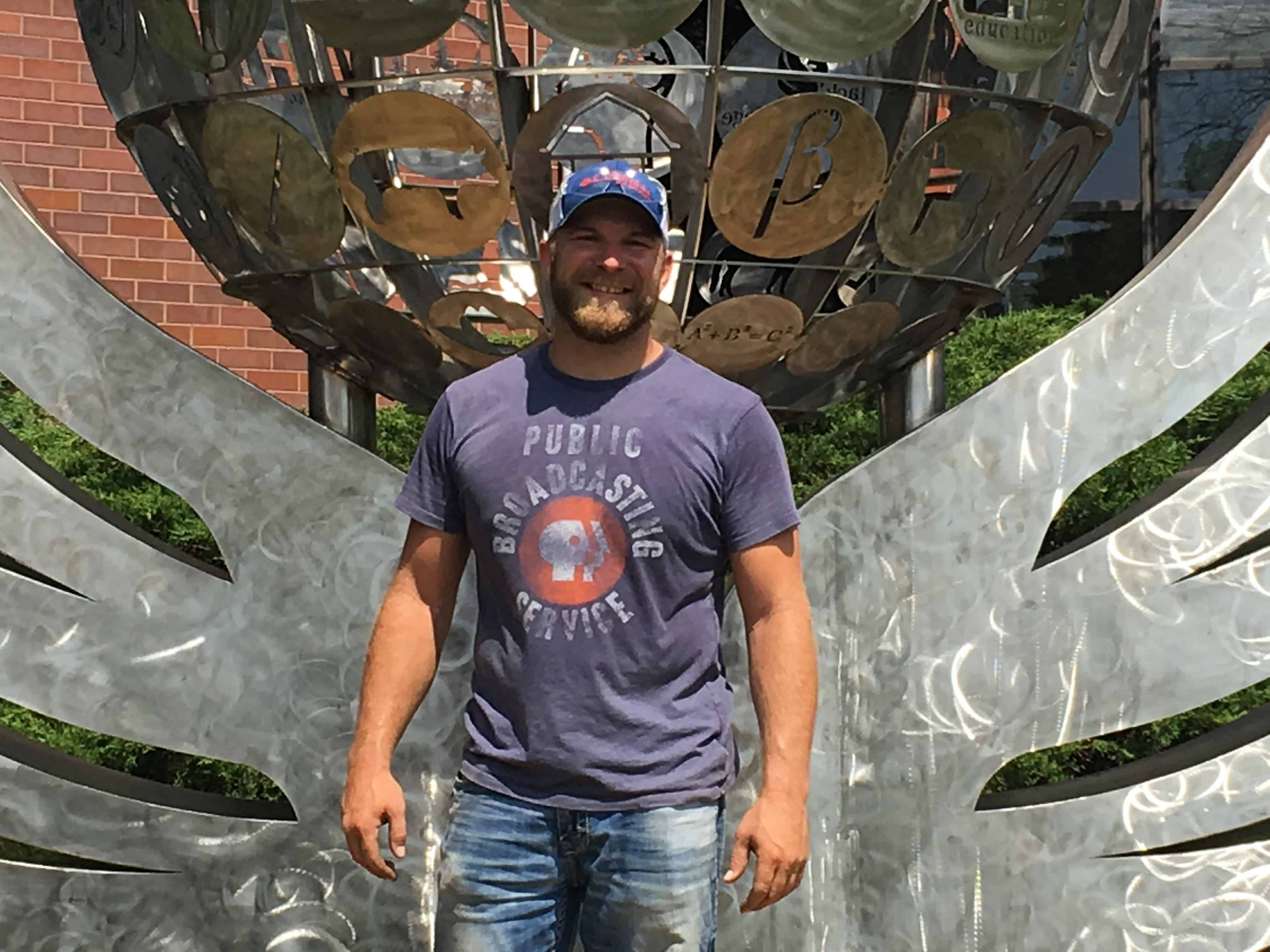 artist Duke Oursler standing in front of Brink - large metal sculpture with globe & wings