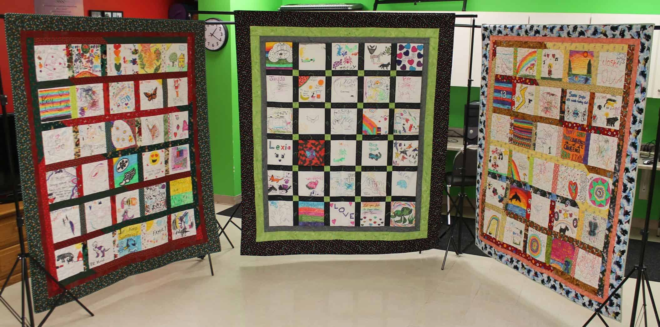display of three quilts