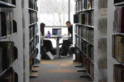 female student and male student studying at table in library between bookstacks