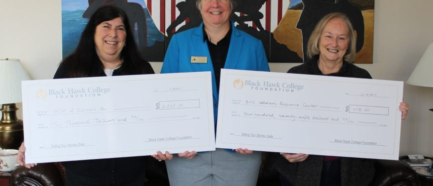 three women holding two oversized checks