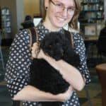 smiling female student holding small black dog