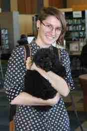 smiling female student holding small black dog