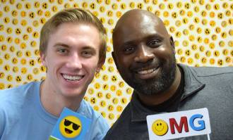 Two male students smiling with emoijis at the student life fair