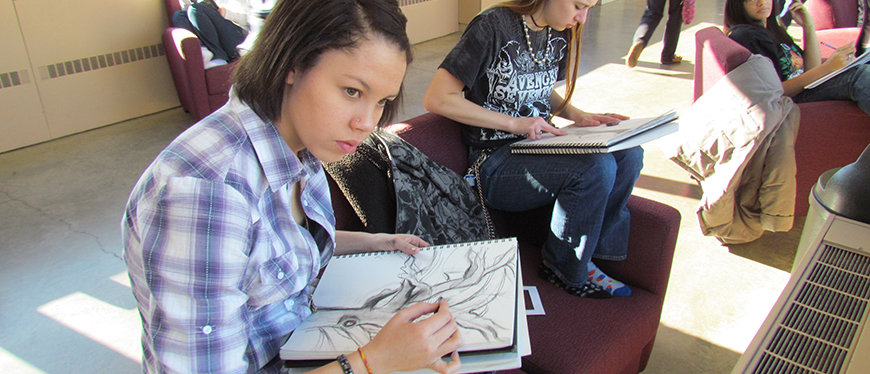 Female art student drawing in the walkway