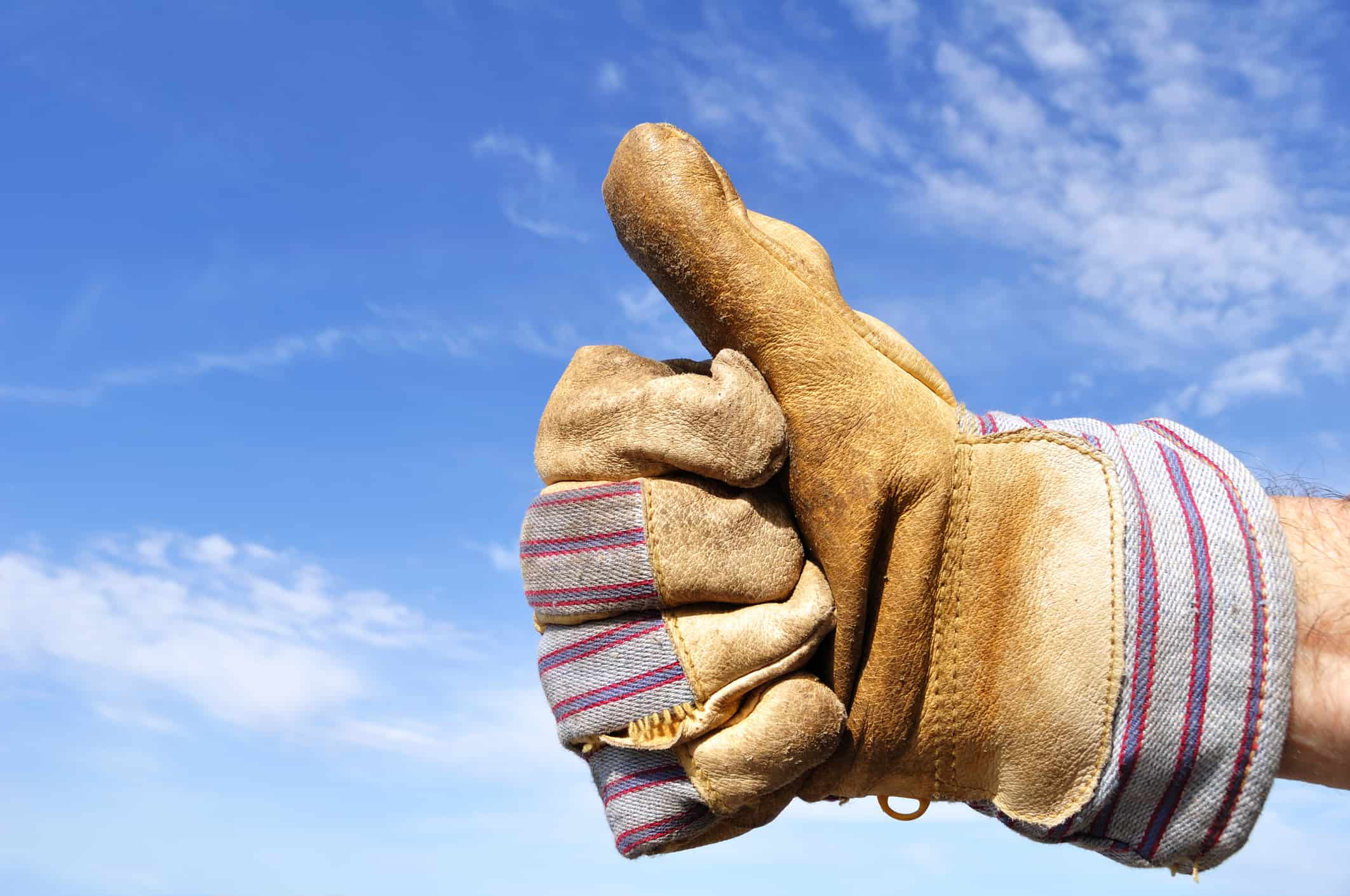 hand in leather work glove giving thumbs up