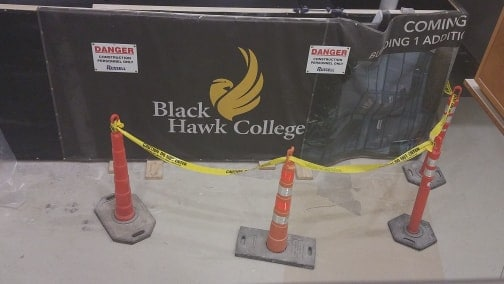 construction cones in front of Black Hawk College banner