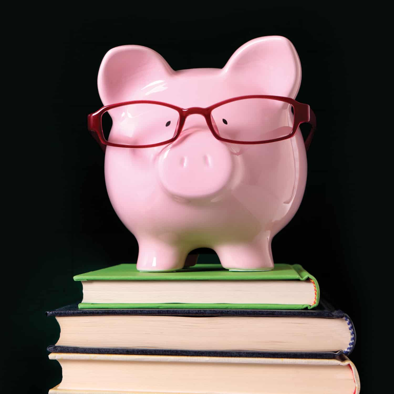 pink piggy bank wearing red glasses on stack of books