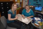 Disability Services employees Alisa Kotaska and Susan Sacco sit at a table